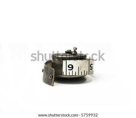 Antique measuring tape in a silver holder - stock photo