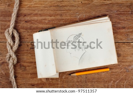 Antique notebook with pencil drawing of woman portrait on wood and rope background - stock photo