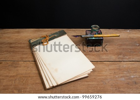 Antique notepad, ink pen and inkwell on wooden table background - stock photo