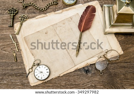 Antique office supplies and accessories on wooden table. Vintage used paper, feather pen. Nostalgic sentimental background - stock photo