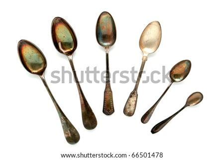 Antique old and tarnished historic soup and dessert silver spoon collection on white