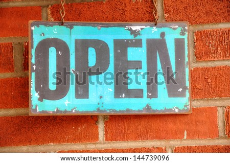 Antique Open Sign Hanging on a Brick Wall - stock photo