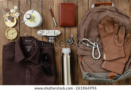 Antique. Overhead view of hiking gear laid out for a backpacking trip on a rustic wood floor. Items include, Backpack, gloves, sweater, camera, film, binoculars, passport, wallet, canteen, compass - stock photo