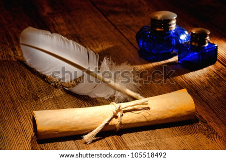 Antique parchment paper sheets roll tied by a string with and old ink writing feather quill and vintage colonial blue glass inkwells on a distressed ancient wood desk - stock photo