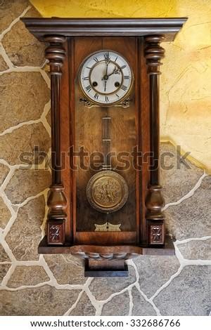 antique pendulum clock hanging on the wall - stock photo