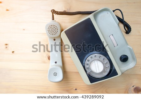 Antique phone on wood background,selective focus point. - stock photo