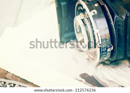 antique photo camera on pile of old photos isolated on white background - stock photo