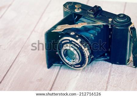 antique photo camera on pile of ols photos isolated on white background - stock photo