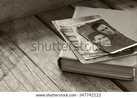 antique photos and old book on wooden table. black and white style photo - stock photo