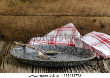Antique plate and silverware photographed on a rustic wooded background. - stock photo
