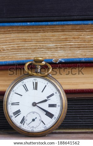 antique pocket  clock close up  on vintage  books background - stock photo