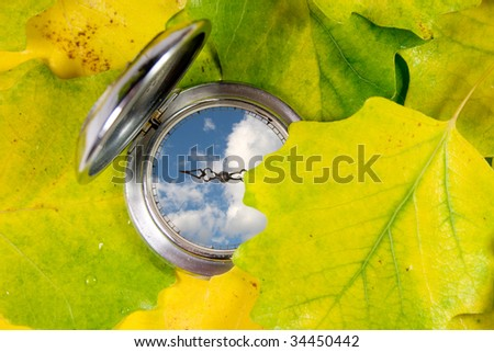 Antique pocket watch covered with yellow autumn leaves (with blue sky and clouds instead of the watch face) - stock photo