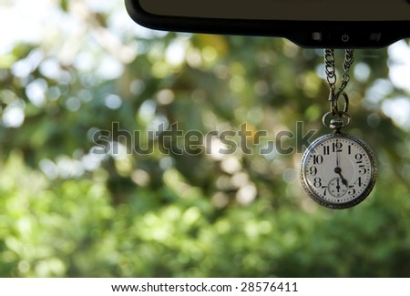 Antique pocket watch hanging from mirror showing five oclock - stock photo