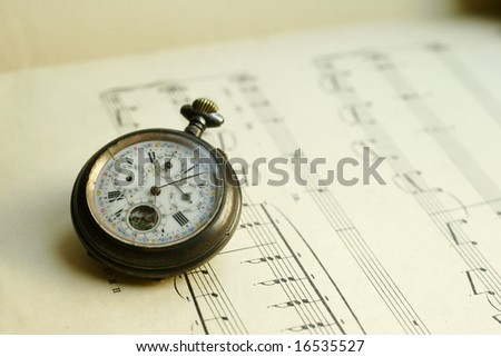 Antique pocket watch laying on music sheet background