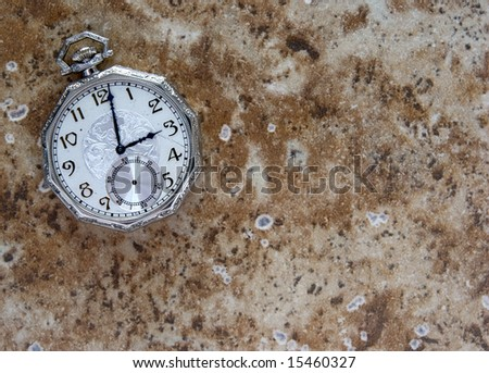 Antique pocket watch on brown grunge background - stock photo