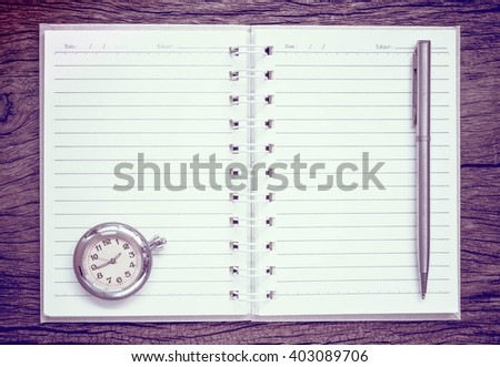 Antique pocket watch on notebook for notes, On old textured wood. Vintage style. - stock photo