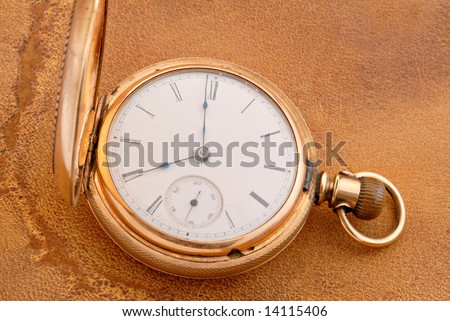 Antique pocket watch resting on old scratched leather. - stock photo