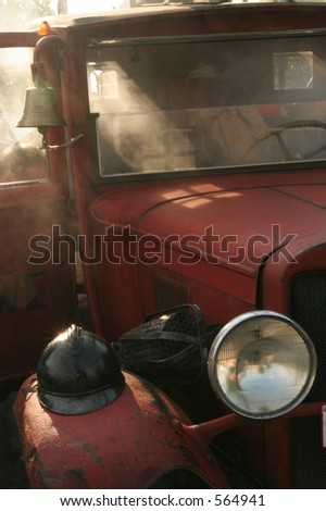 Antique red fire truck in a smokey scene