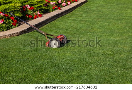 Antique reel mower on pristine green lawn with flower bed in background. - stock photo