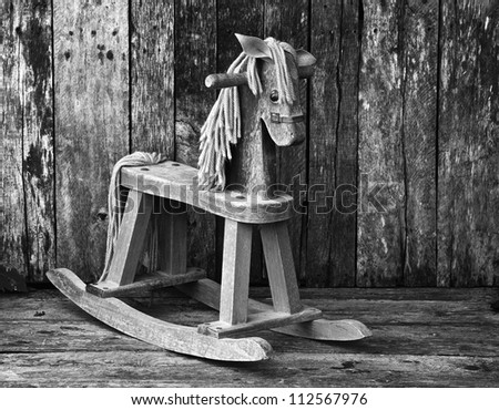 Antique rocking horse on a rustic country backdrop, desaturated.. - stock photo