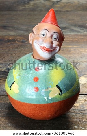 antique roly-poly doll on wooden background - stock photo