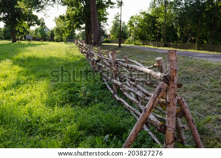 antique rustic rural style twisted fence of thin branches along the road  - stock photo