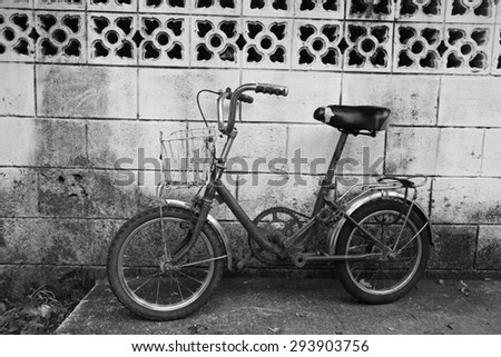 Antique rusty bicycle near the wall. Black and white concept - stock photo