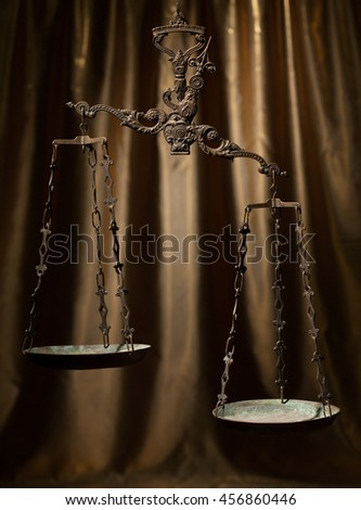 Antique rusty weighing scale on golden background. - stock photo