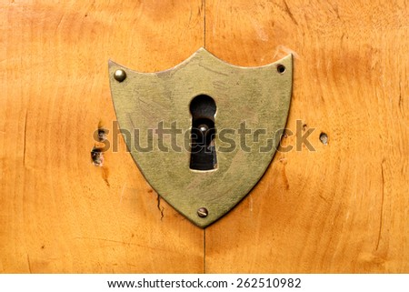 Antique shield-shaped lock on bright cherry wood, frontal view