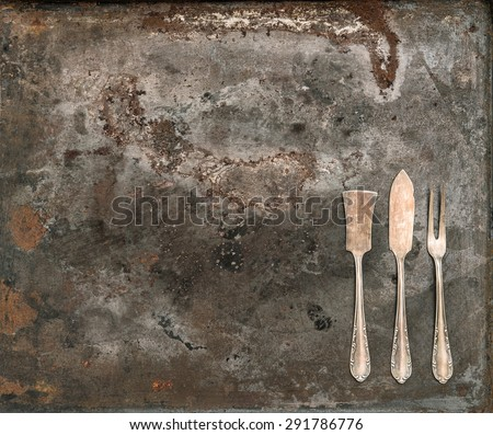 Antique silver cutlery on rustic metal background. Vintage tableware. Retro style toned picture - stock photo