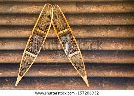 Antique Snow Shoes mounted on wall of log cabin. Copy space. - stock photo
