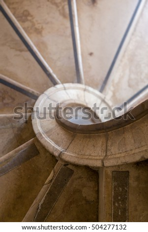antique spiral ladder from marble stone in day light