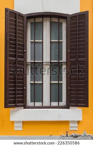 Antique style window on yellow wall