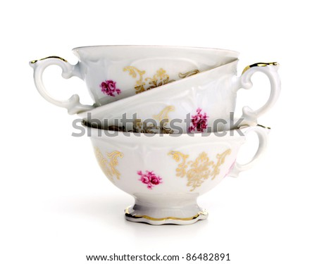 Antique tea cups stack on white background - stock photo