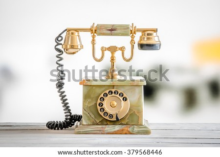 Antique telephone in gold and marble on a wooden desk - stock photo