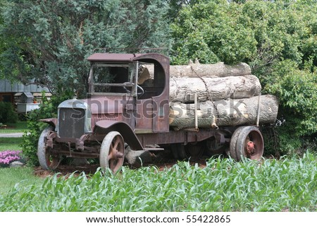 antique truck with load of logs - stock photo
