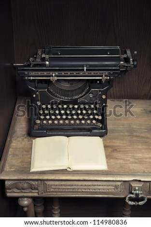 Antique typewriter on desk with book - stock photo