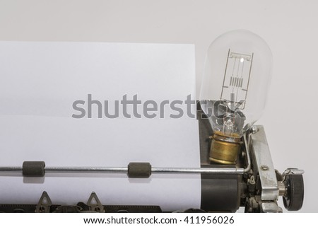 antique typewriter with an old light bulb - stock photo