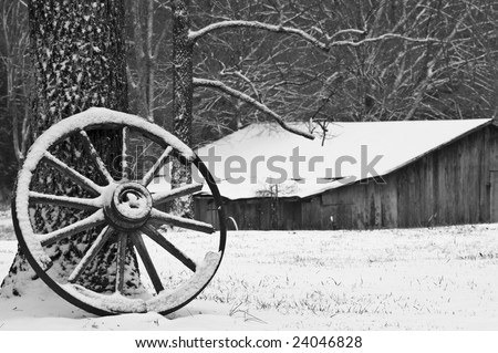 Antique wagon wheel leaning against a tree in light snow. - stock photo