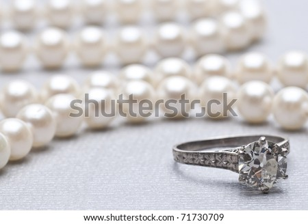 Antique Wedding Ring and Pearls with Focus on Ring. - stock photo