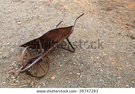 Antique wheelbarrow used in gold mining activities. - stock photo