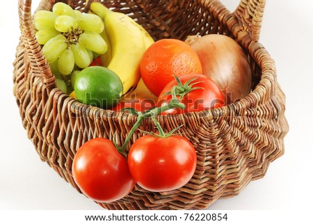 Antique wicker basket filled with fresh fruit and vegetables -  tomatoes, grapes, lemon, lime, onion, bananas and tangelos.