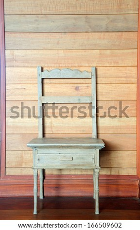 antique wood chair against wooden wall