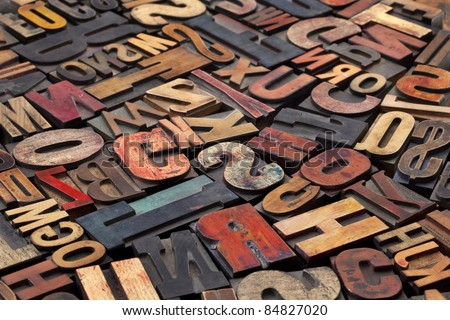 antique wood letterpress printing blocks with color ink patina, random collection of different size and style - stock photo