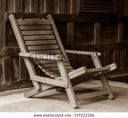 Antique wooden arm chair and old wooden background. - stock photo