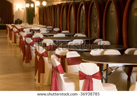 Antique wooden barrels in an old arched wine cellar in a catering event. - stock photo
