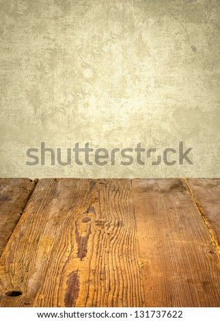 antique wooden table in front of weathered wall - stock photo