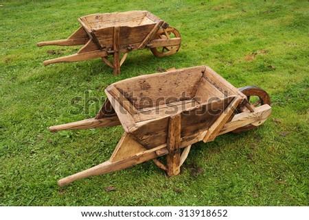Antique wooden wheelbarrows on grass - stock photo