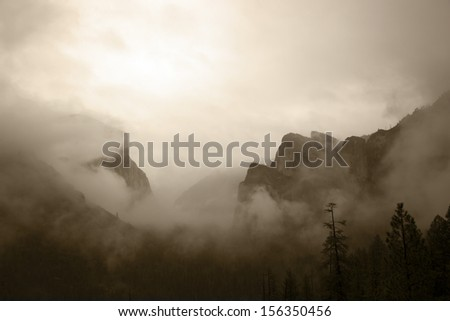 Antiqued view of Yosemite Valley under heavy Winter storm clouds.