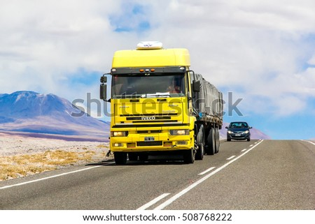 ANTOFAGASTA, CHILE - NOVEMBER 15, 2015: Yellow semi-trailer truck Iveco EuroTech at the interurban road through the Atacama desert.